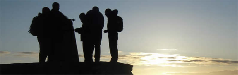 Jubilant group standing beside summit trig point on Ben Nevis as dawn is breaking